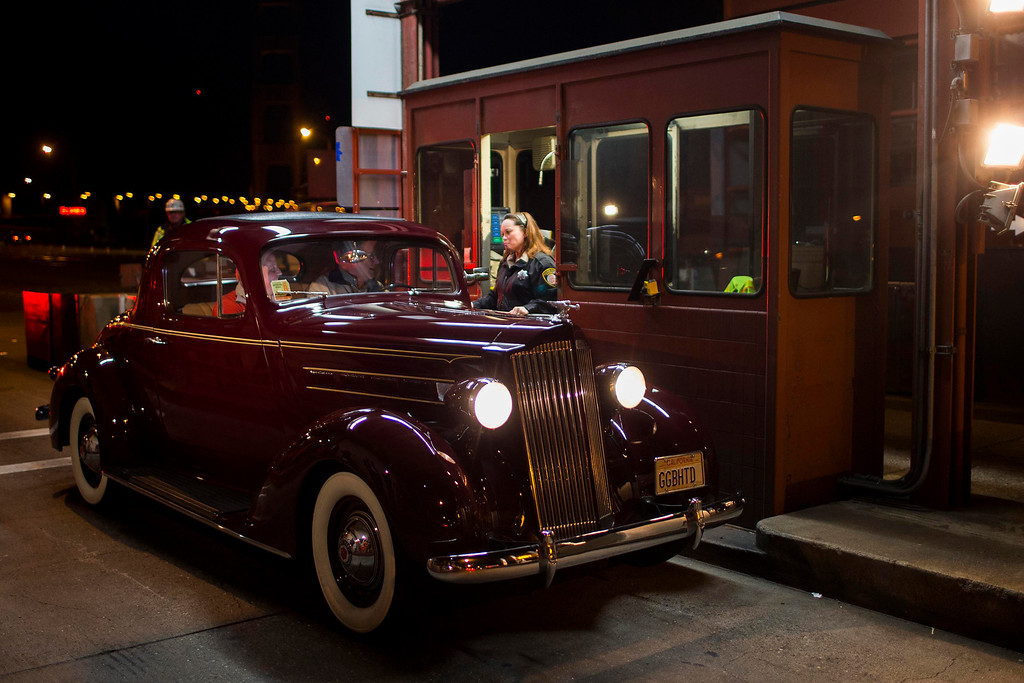 . Toll collector Marilyn Alvardo (R) receives the last toll from Jim Eddie (C), who is driving a vintage 1937 Packard, at her tollbooth at the Golden Gate Bridge toll plaza in San Francisco, California March 27, 2013. The Golden Gate Bridge will convert from manned tollbooths to a full electronic tolling system starting March 27. With the automated system in place, motorists will have the option of using the existing FasTrak electronic toll collection system or the newly implemented pay-by-plate option, according to Golden Gate Bridge management. REUTERS/Stephen Lam
