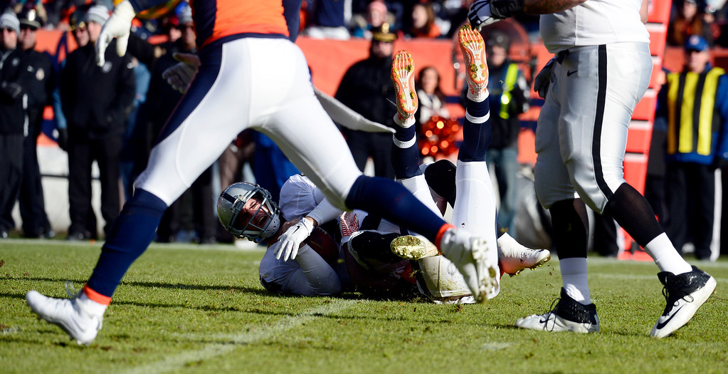 . DENVER, CO - DECEMBER 28: Aqib Talib (21) of the Denver Broncos sacks Derek Carr (4) of the Oakland Raiders in the first quarter.  The Denver Broncos played the Oakland Raiders at Sports Authority Field at Mile High in Denver on December, 28 2014. (Photo by Tim Rasmussen/The Denver Post)