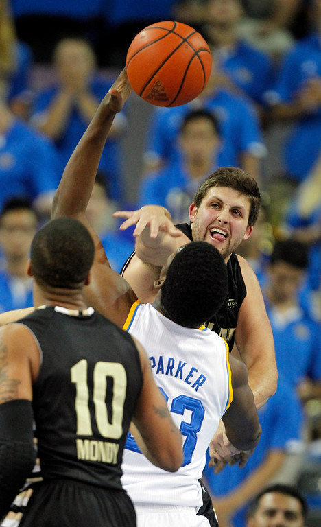 . Oakland center Corey Petros, top, blocks a shot by UCLA center Tony Parker, center, with Oakland guard Duke Mondy (10) defending in the first half of an NCAA college basketball game Tuesday, Nov. 12, 2013, in Los Angeles. (AP Photo/Alex Gallardo)