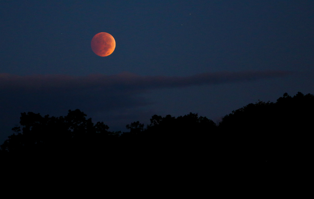 . A lunar eclipse appears above Roanoke Valley on Wednesday, Oct. 8, 2014 in Roanoke, Va.  The moon appears orange or red as it reflects the suns color in the Earth\'s atmosphere. This is known as the blood moon. (AP Photo/The Roanoke Times, Stephanie Klein-Davis)