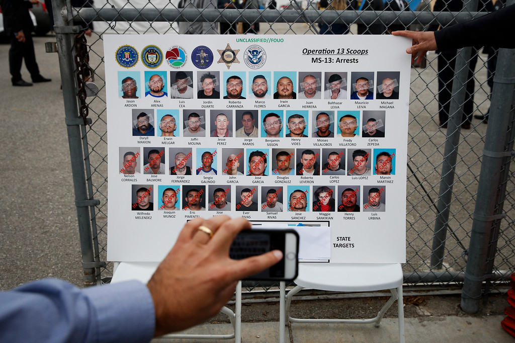 . A reporter uses his smartphone to photograph a board showing images of MS-13 gang members during a news conference Wednesday, May 17, 2017, in Los Angeles. Hundreds of federal and local law enforcement fanned out across Los Angeles, serving arrest and search warrants as part of a three-year investigation into the violent and brutal street gang MS-13. (AP Photo/Jae C. Hong)