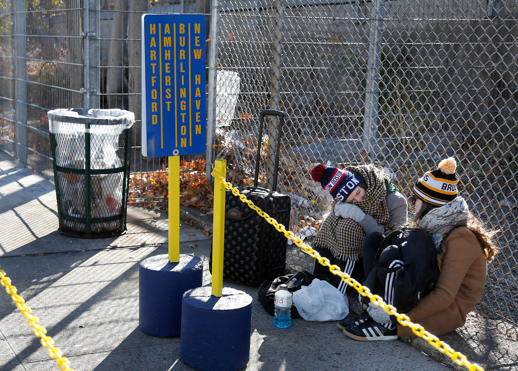 . Travelers sit on the ground while waiting to board a bus in New York, Wednesday, Nov. 23, 2016. Almost 49 million people are expected to travel 50 miles or more for the Thanksgiving holiday, the most since 2007, according to AAA. (AP Photo/Seth Wenig)