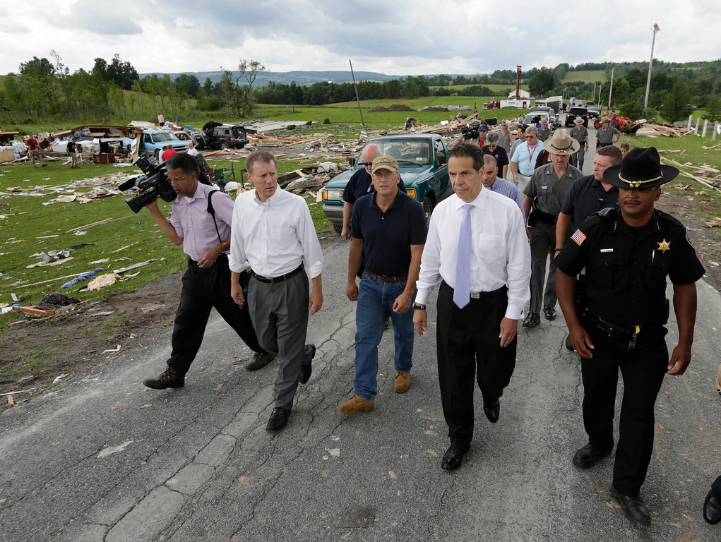 . New York Gov. Andrew Cuomo, second from right, walks with state Sen. David Valesky, left, Smithfield Town Supervisor Rick Bargabos and Madison County Sheriff Allen Riley as they survey the damage from Tuesday night\'s storm, on Wednesday, July 9, 2014, in Smithfield, N.Y. (AP Photo/Mike Groll)