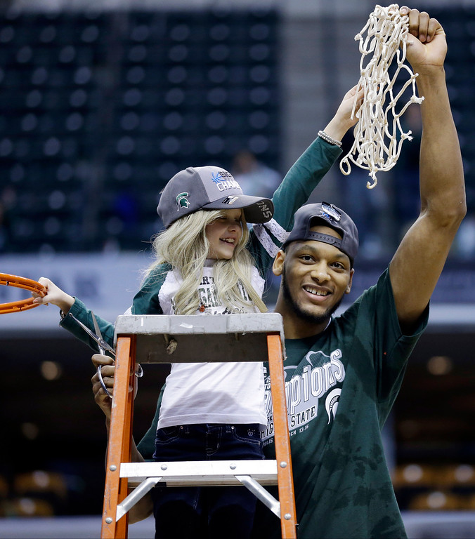 ". FILE - In this March 16, 2014 file photo, Michigan State forward Adreian Payne, right, hoists the net with Lacey Holsworth, who is battling cancer, after Michigan State defeated Michigan 69-55 in an NCAA college basketball game in the championship of the Big Ten Conference tournament in Indianapolis. The father of  8-year-old Lacey Holsworth, who befriended Michigan State basketball star Adreian Payne says his daughter has died. Matt Holsworth says Lacey Holsworth died at their St. Johns, Mich., home late Tuesday, April 8, 2014 ""with her mommy and daddy holding her in their arms.\"" (AP Photo/Michael Conroy, File)"