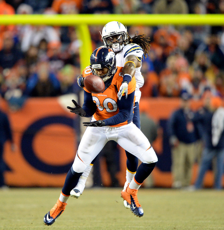 . Denver Broncos tight end Julius Thomas (80) makes a catch and is taken down by San Diego Chargers defensive back Jahleel Addae (37) in the first quarter.  The Denver Broncos vs. the San Diego Chargers at Sports Authority Field at Mile High in Denver on December 12, 2013. (Photo by Hyoung Chang/The Denver Post)