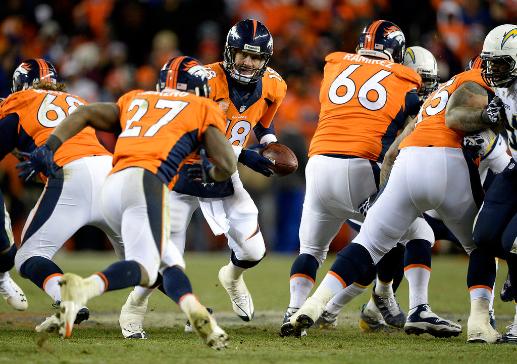 . Denver Broncos quarterback Peyton Manning (18) hands off to Denver Broncos running back Knowshon Moreno (27) during the fourth quarter. The Denver Broncos vs. The San Diego Chargers in an AFC Divisional Playoff game at Sports Authority Field at Mile High in Denver on January 12, 2014. (Photo by John Leyba/The Denver Post)