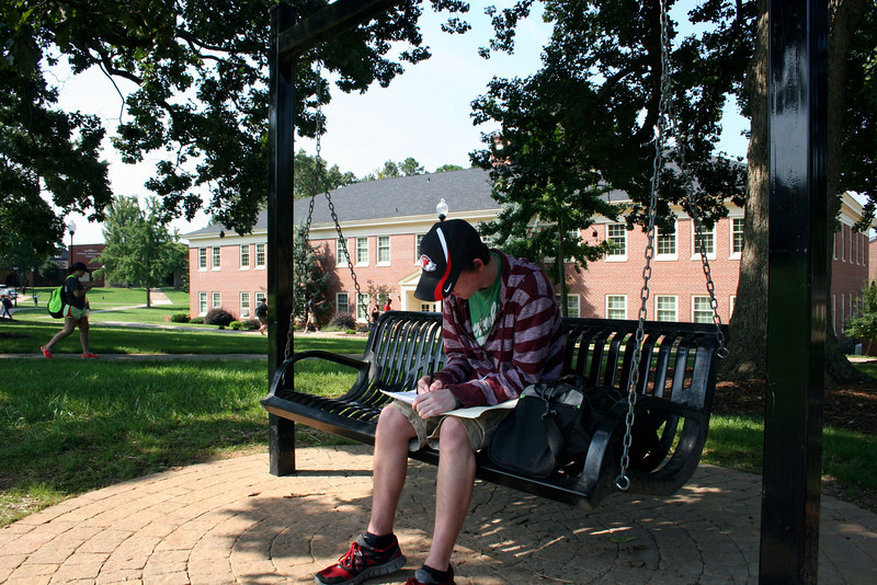A Gardner-Webb University student studies on a bench before going to class.