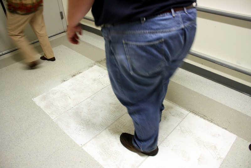 Visitors to the Flight Hardware Processing Area must walk across sticky paper to remove contaminants on their shoes
