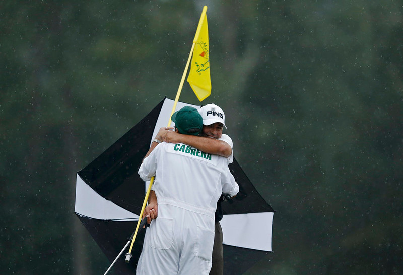 . Angel Cabrera of Argentina (R) hugs his son, caddie Angel Cabrera Jr. after sinking a birdie putt on the 18th green during final round play in the 2013 Masters golf tournament at the Augusta National Golf Club in Augusta, Georgia, April 14, 2013.   REUTERS/Phil Noble