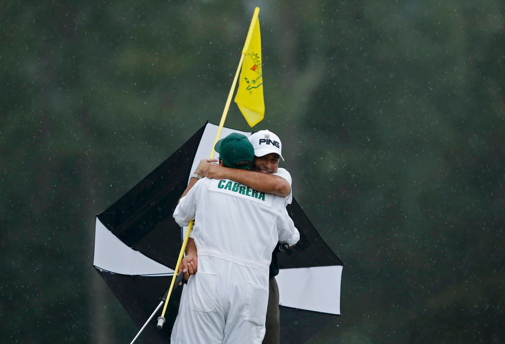 Description of . Angel Cabrera of Argentina (R) hugs his son, caddie Angel Cabrera Jr. after sinking a birdie putt on the 18th green during final round play in the 2013 Masters golf tournament at the Augusta National Golf Club in Augusta, Georgia, April 14, 2013.   REUTERS/Phil Noble