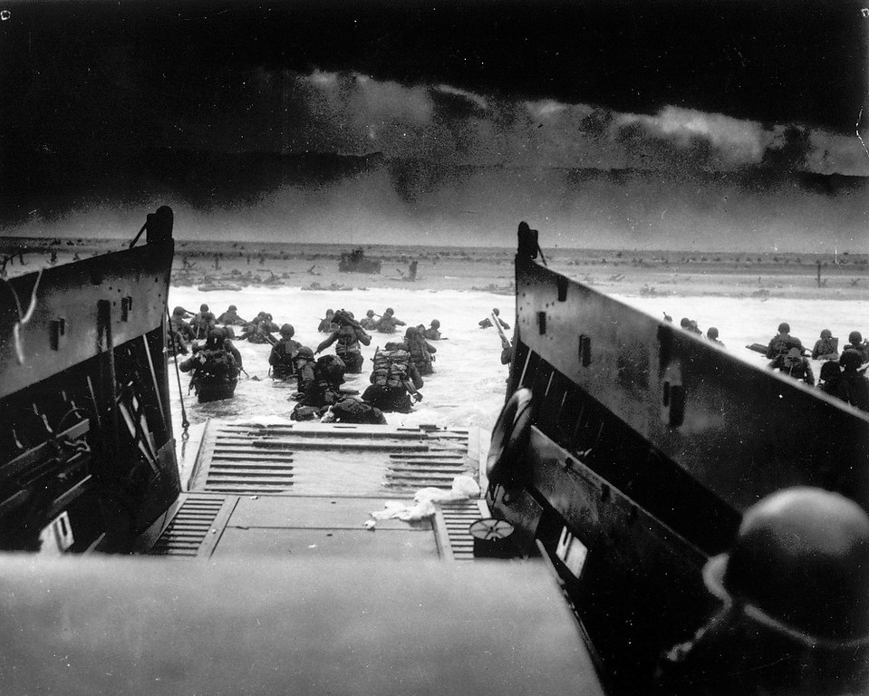 . While under attack of heavy machine gun fire from the German coastal defense forces, these American soldiers wade ashore off the ramp of a U.S. Coast Guard landing craft, June 6, 1944, during the Allied landing operations at the Normandy. (AP Photo)