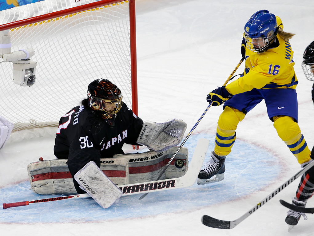 . Goalkeeper Nana Fujimoto of Japan blocks Pernilla Winberg\'s  of Sweden shot ate the goal during the 2014 Winter Olympics women\'s ice hockey game at Shayba Arena, Sunday, Feb. 9, 2014, in Sochi, Russia. (AP Photo/Matt Slocum)