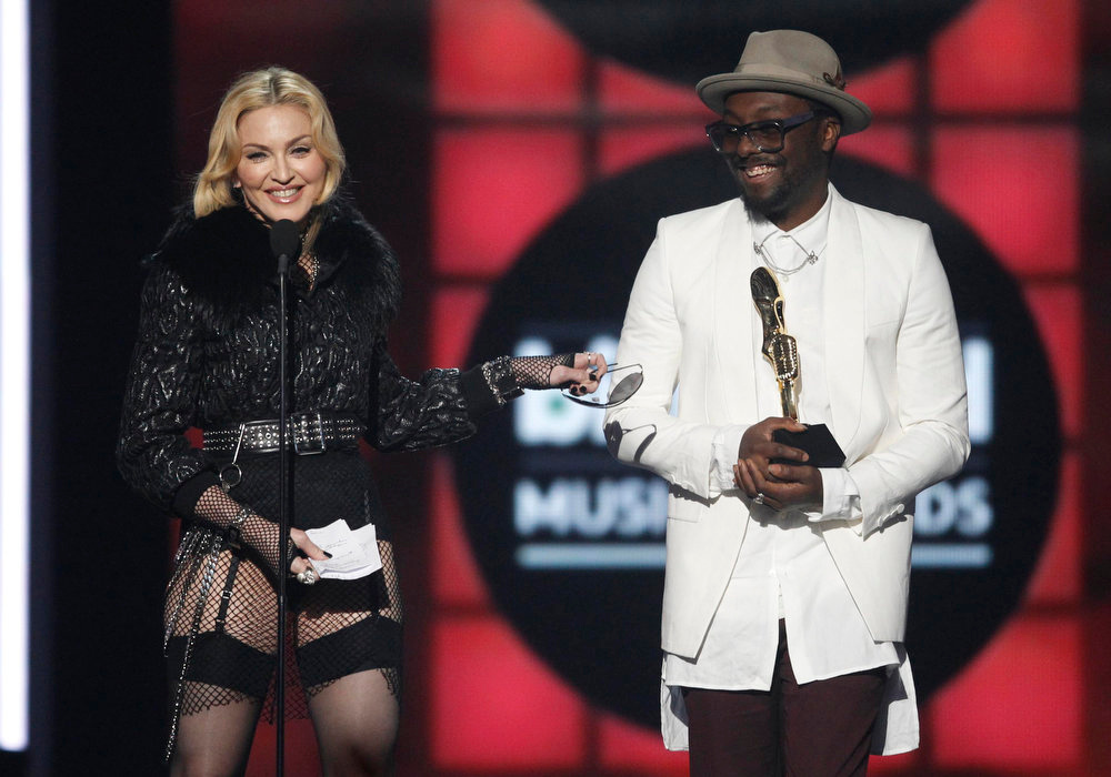 ". Singer Madonna accepts the award for ""Top Touring Artist\"" presented to her by musician Will.i.am (R), during the Billboard Music Awards at the MGM Grand Garden Arena in Las Vegas, Nevada May 19, 2013. REUTERS/Steve Marcus"