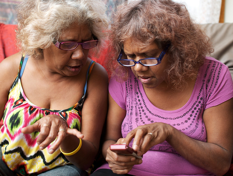 Two Aboriginal Women gathered around Mobile Phone