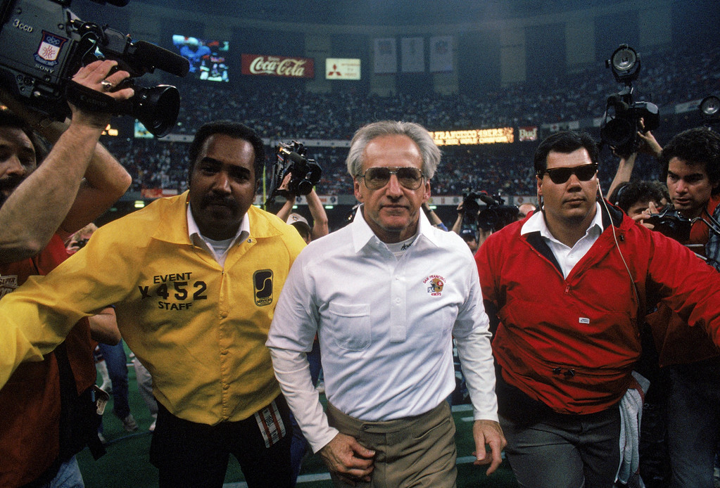 . Head coach George Seifert of the San Francisco 49ers gets an escort to the locker room after defeating the Denver Broncos in Super Bowl XXIV at Louisiana Superdome on January 28, 1990 in New Orleans, Louisiana.  The 49ers won 55-10.  (Photo by George Rose/Getty Images)