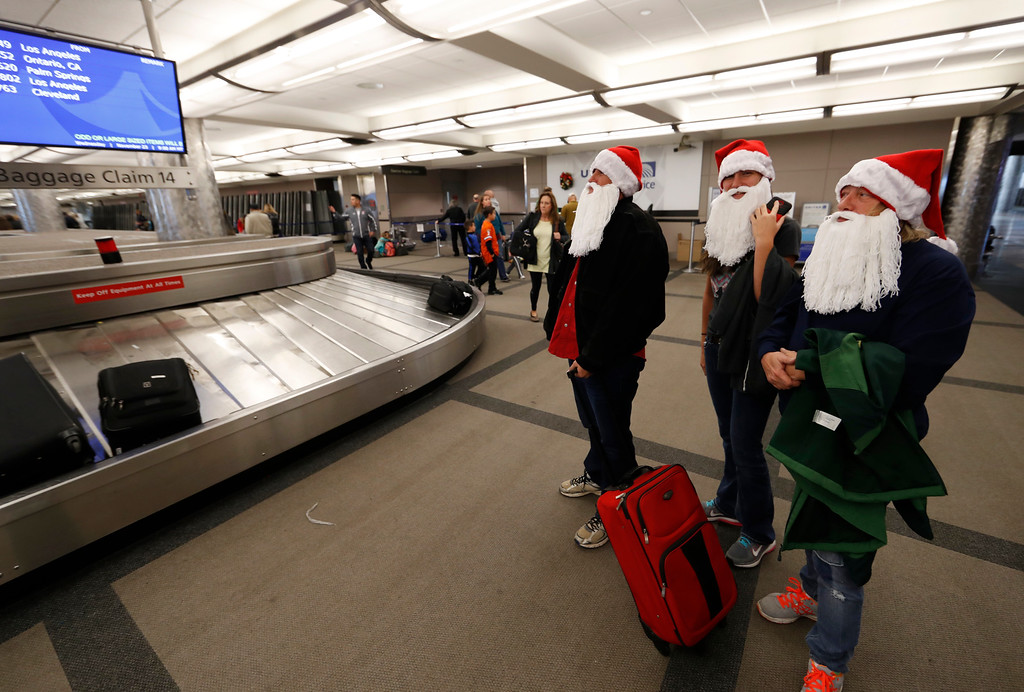 . Dressed in Santa Claus beards and Christmas hats, Kristi, left, and her daughter, Lacee Bartukus, join Laura Kearney, all of Thomson, Ga., in waiting for their luggage at Denver International Airport early Wednesday, Nov. 23, 2016, in Denver. Travelers are criss-crossing the country Wednesday, clogging airport terminals in a rush to reach their Thanksgiving Day destinations. (AP Photo/David Zalubowski)