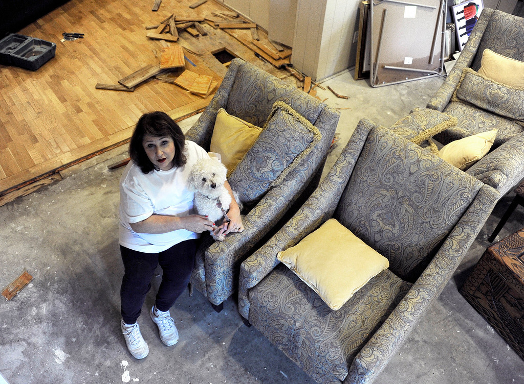 . Randi Rosenkrantz holds her dog Sugar as she talks about the flood damage to her home Wednesday, May 27, 2015, in Houston. Heavy rains have caused flooding and closure of sections of highways in the Houston area and across Texas. (AP Photo/Pat Sullivan)