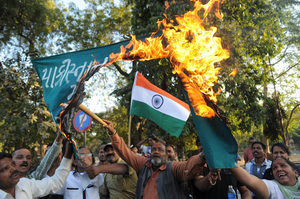 ". Indian demonstrators burn a banner which reads ""Down with Pakistan, Shame on Pakistan\"" as an Indian flag is pictured in the background as they demonstrate against the alleged killing of two Indian soldiers by Pakistan in the disputed Kashmir region, in Ahmedabad on January 10, 2013.  Pakistan on January 10 accused Indian troops of opening fire and killing a Pakistani soldier, the third deadly cross-border incident in days that threatens to escalate tensions in Kashmir. SAM PANTHAKY/AFP/Getty Images"