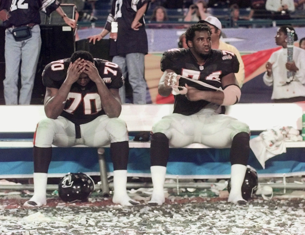 . Atlanta Falcons Bob Whitfield (70) and Ephraim Salaam (74) sit on the bench surrounded by confetti following their 34-19 loss to the Denver Broncos in Super Bowl XXXIII in Miami, Sunday, Jan. 31, 1999. (AP Photo/John Bazemore)