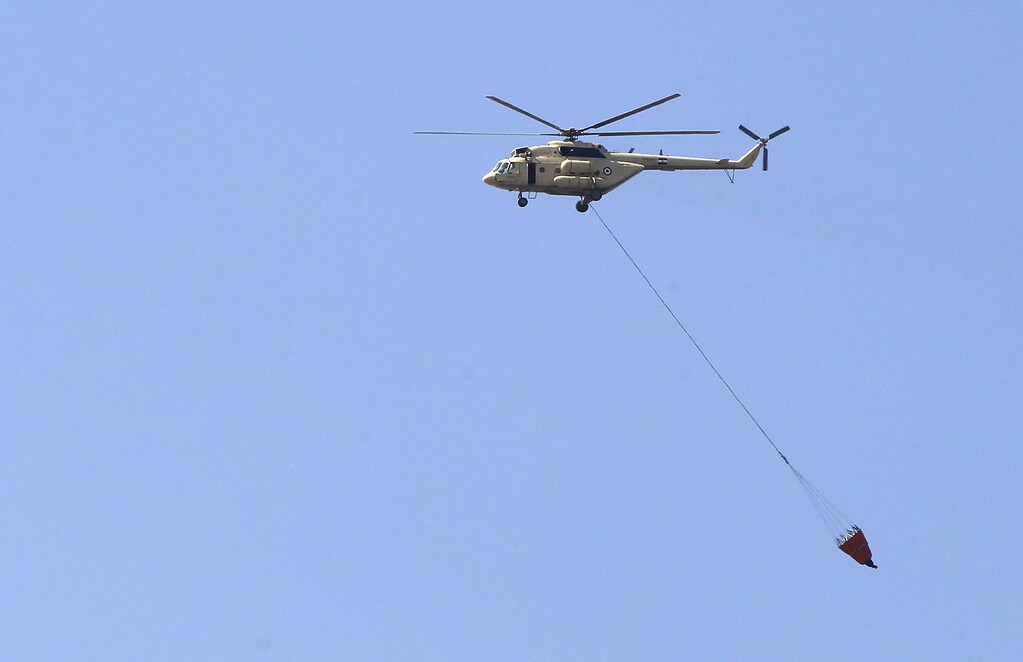 """. An Egyptian army helicopter transports water to hose down fires at a police officers\' club and the Egyptian Soccer Federation after Al Ahly fans, also known as \""""Ultras\"""" set fire to them following a court verdict, in Cairo March 9, 2013.  REUTERS/Amr Abdallah Dalsh"""