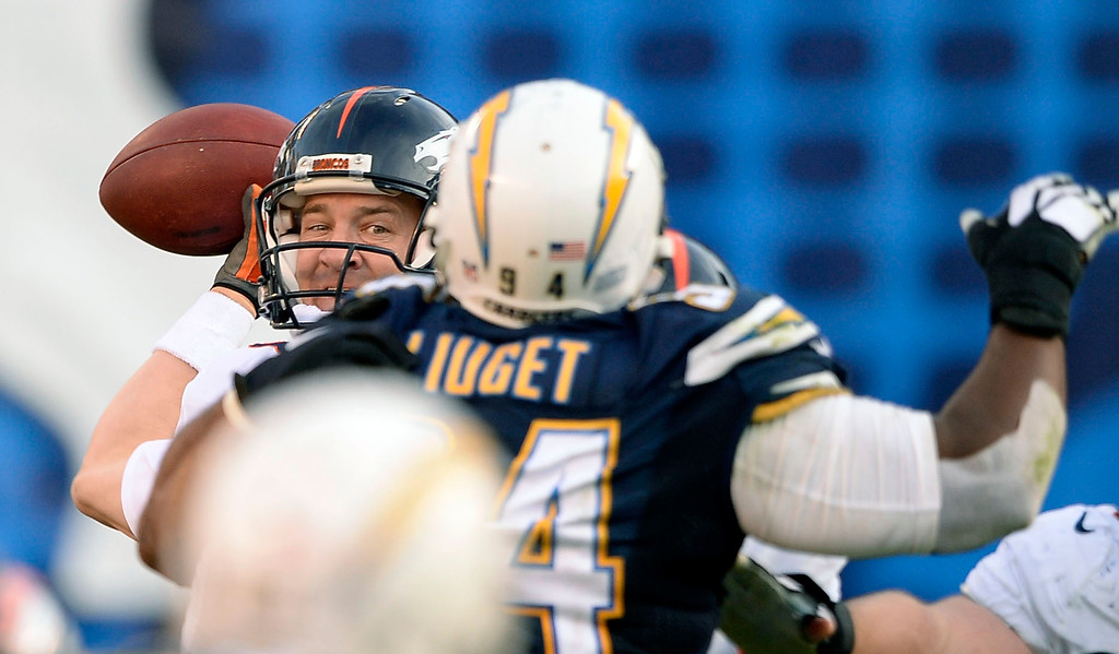 . SAN DIEGO, CA - DECEMBER 14: Denver Broncos quarterback Peyton Manning (18) looks to throw over San Diego Chargers defensive end Corey Liuget (94) during the third quarter December 14, 2014 at Qualcomm Stadium (Photo By John Leyba/The Denver Post)