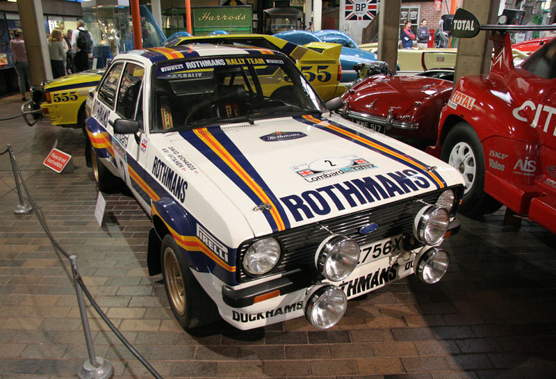 The famous Rothmans Escort of Ari Vaternen and David Richards, National Motor Museum, Beaulieu, Southern England. In behind the yellow Audi Quattro is Malcolm Campbell's Bluebird.