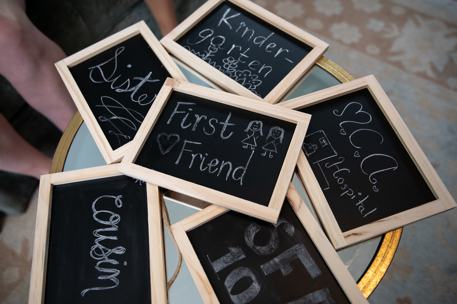 a pile of chalkboard signs that read first friend cousin sister kindergarten MCA hospital
