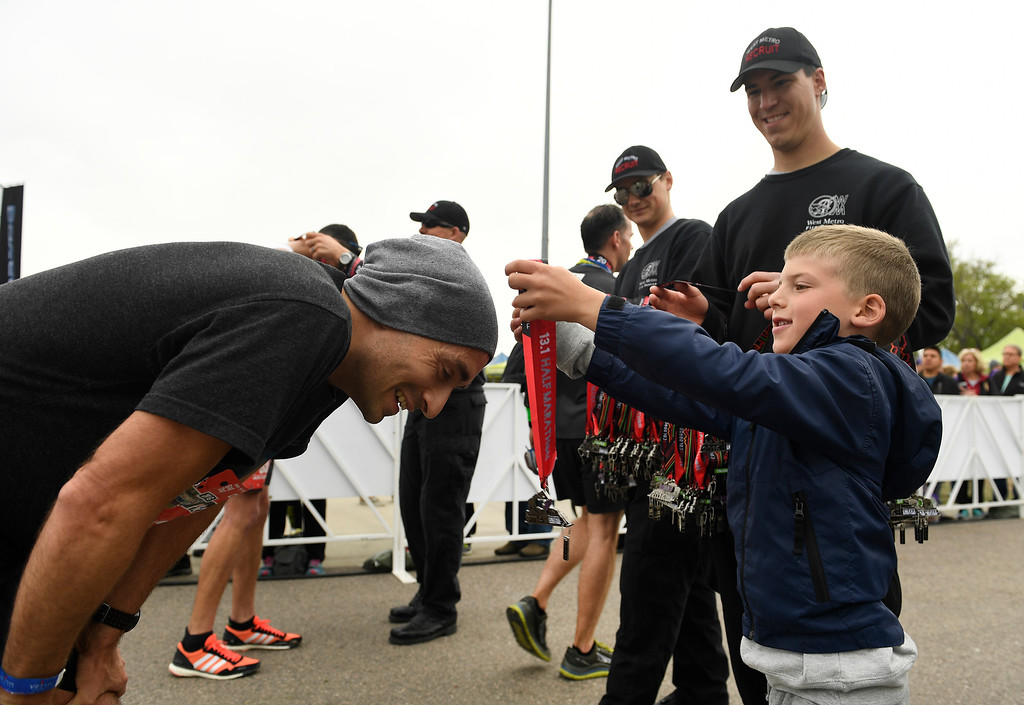 . DENVER, CO - MAY 15: Hunter Christy, 6, with his father Firefighter Rob Christy helping, in back,  gives a runner his  race medal after finishing the Colfax Half Marathon during the 11th annual Colfax Half Marathon on May 15, 2016 in Denver, Colorado.  Thousands of runners took part in the annual springtime race which included a marathon, a marathon relay,  a half marathon and the urban 10 miler.  (Photo by Helen H. Richardson/The Denver Post)