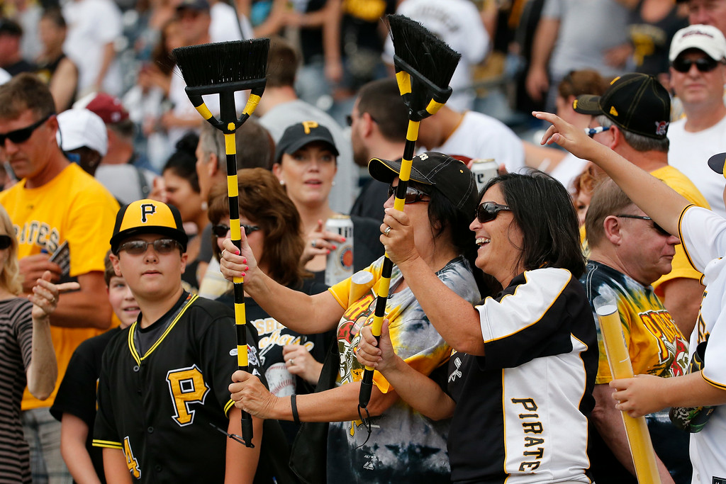 . Pittsburgh Pirates fans wave brooms after the Pirates completed a three-game sweep of the Colorado Rockies in a baseball game in Pittsburgh Sunday, July 20, 2014. The Pirates won 5-3. (AP Photo/Gene J. Puskar)