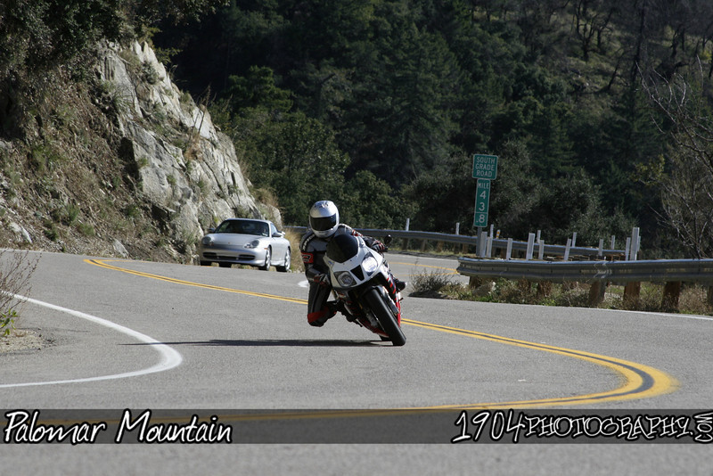 A honda RC-51 heads up south grade road as a Porsche trails in the background on palomar mountain.