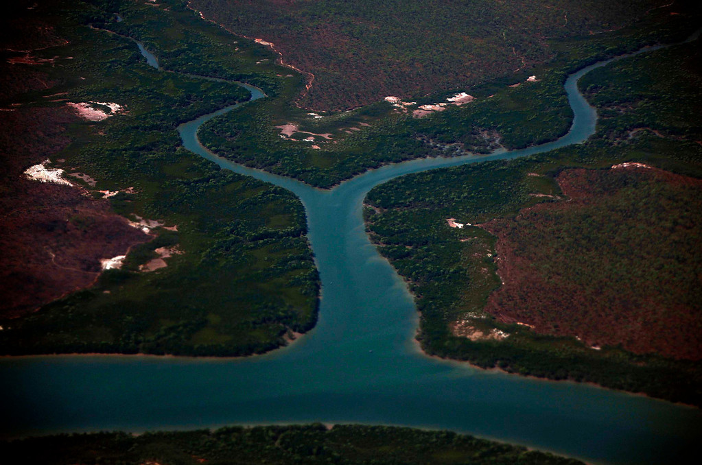 . A river and its estuaries are seen surrounded by mangroves in Arnhem Land in Australia\'s Northern Territory July 15, 2013. Australia\'s North West Mobile Force, known as NORFORCE, is a surveillance unit that employs ancient Aboriginal skills to help in the seemingly impossible task of patrolling the country\'s vast northwest coast. NORFORCE\'s area of operations is about 1.8 million square km (700,000 square miles), covering the Northern Territory and the north of Western Australia. Aboriginal reservists make up a large proportion of the 600-strong unit, and bring to bear their knowledge of the land and the food it can provide. Fish, shellfish, turtle eggs and even insects supplement rations during the patrol, which is on the lookout for illegal foreign fishing vessels and drug smugglers, as well as people smugglers from neighboring Indonesia. Picture taken July 15, 2013.   REUTERS/David Gray