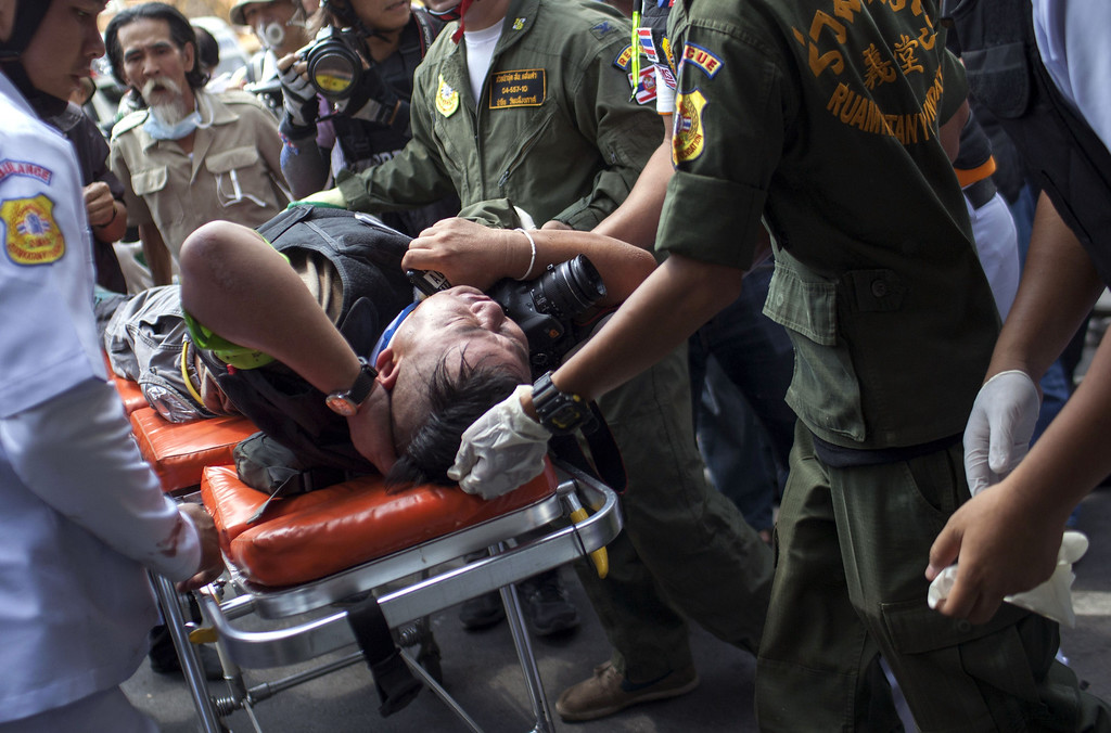 . A press photographer is helped by medical personnel after being injured during clashes between police and anti-government protesters near Phan Fah Bridge in Bangkok on February 18, 2014.  AFP PHOTO / KC Ortiz/AFP/Getty Images