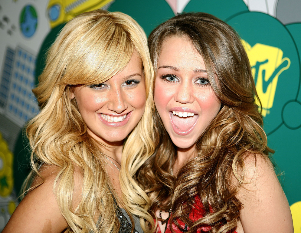 """. Actresses Ashley Tisdale, left, and Miley Cyrus pose backstage during MTV\'s \""""Total Request Live\"""" , Tuesday, June 20, 2006, in New York.  Tisdale stars in \""""The Suite Life of Zack & Cody\""""  and Cyrus stars in \""""Hannah Montana\"""" , both on the Disney Channel.  (AP Photo/Jason DeCrow)"""