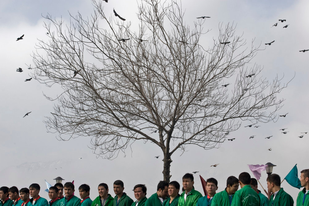 . Afghan men wait to see the holy flag, at the Kart-e Sakhi mosque in Kabul, Afghanistan, Thursday, March 21, 2013. According to local belief, the country\'s fortune in the New Year depends on the ability of the men to erect the pole. Afghanistan celebrates Nowruz, marking the first day of spring and the beginning of the year on the Iranian calendar. (AP Photo/Ali Hamed Haghdoust)
