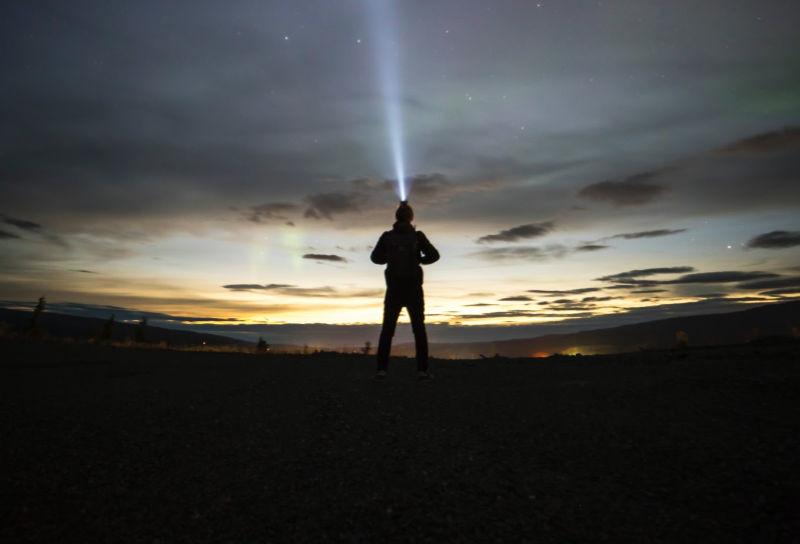 Person shining headlamp at sunrise