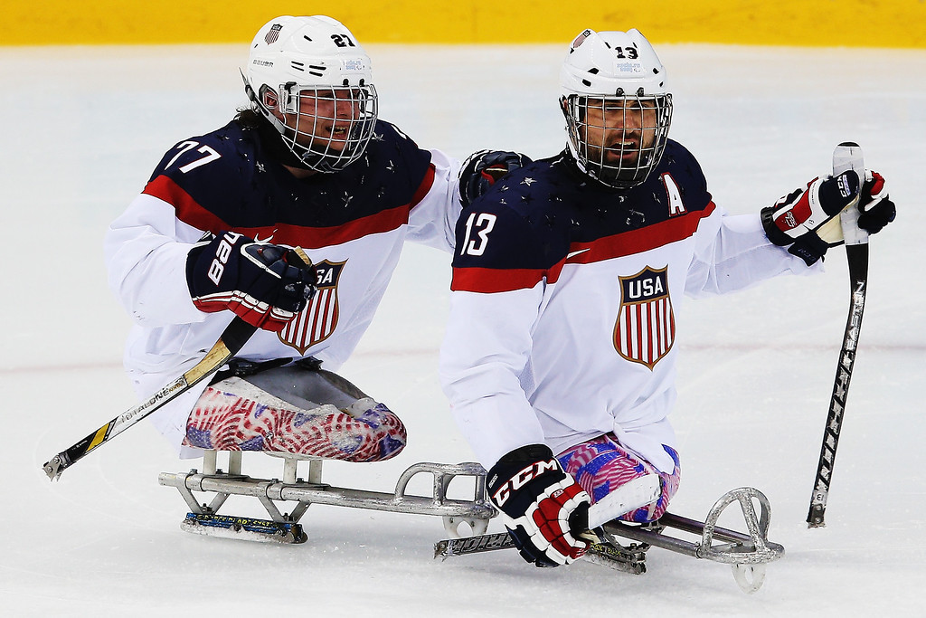 . Joshua Sweeney of the USA celebrates with Joshua Pauls of the USA after scoring a goal during the ice sledge hockey gold medal game between the Russian Federation and the United States of America at the Shayba Arena during day eight of the 2014 Paralympic Winter Games on March 15, 2014 in Sochi, Russia.  (Photo by Hannah Peters/Getty Images)