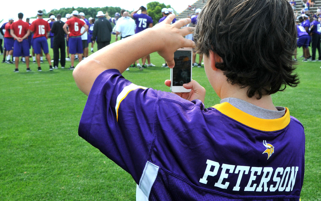 . Aidan Smith, 9, of Minneapolis uses his smartphone to get a picture of his jersey\'s namesake and other Vikings favorites during the team\'s morning drills.   (Pioneer Press: John Doman)