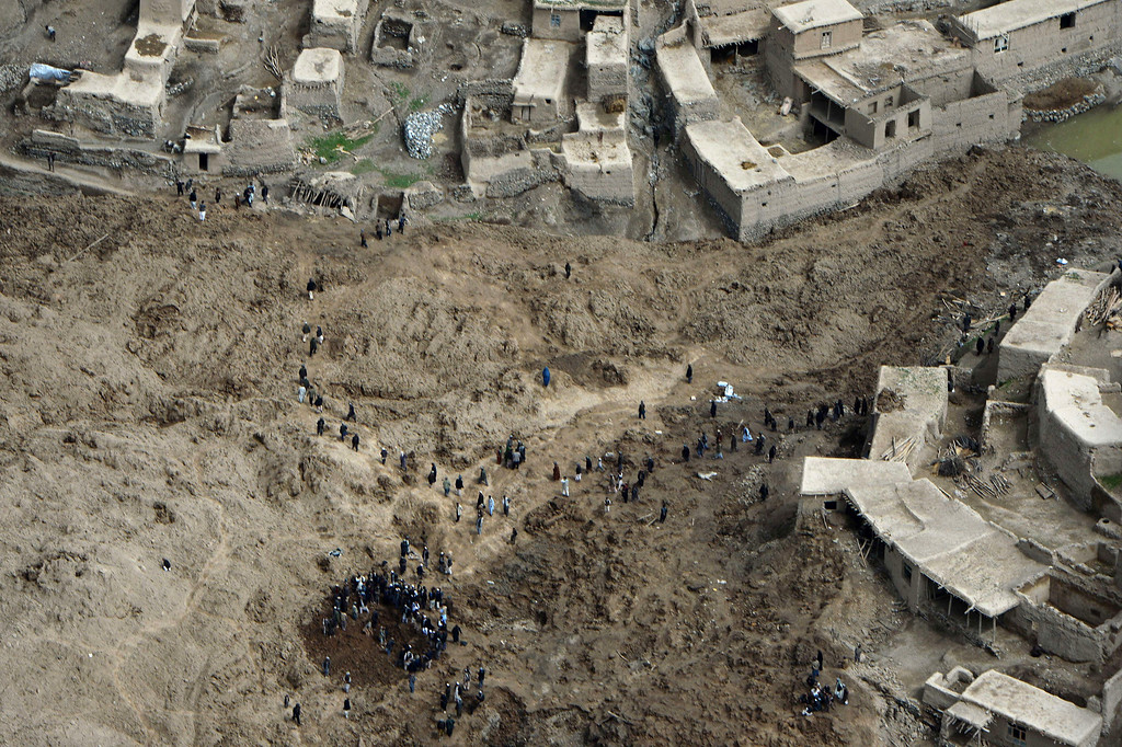 . Afghan villagers gather dig through the mud and rocks of a landslide in Aab Bareek village at Argo district of Badakhshan on May 5, 2014. AFP PHOTO/WAKIL KOHSAR/AFP/Getty Images