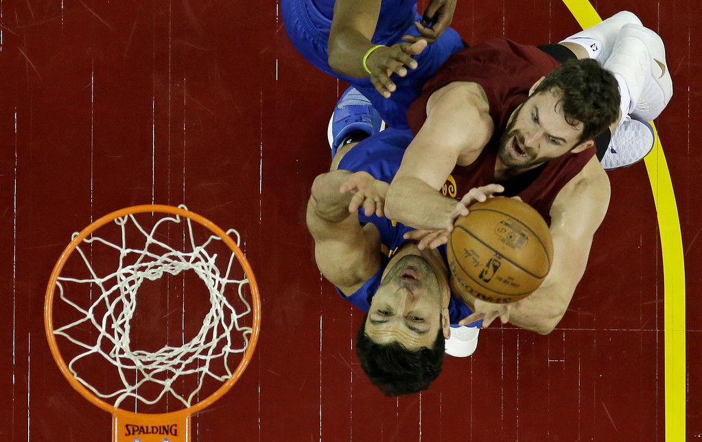 . Cleveland Cavaliers\' Kevin Love, right, drives to the basket against Golden State Warriors\' Zaza Pachulia, from Republic of Georgia, in the first half of an NBA basketball game, Sunday, Dec. 25, 2016, in Cleveland. The Cavaliers won 109-108. (AP Photo/Tony Dejak)
