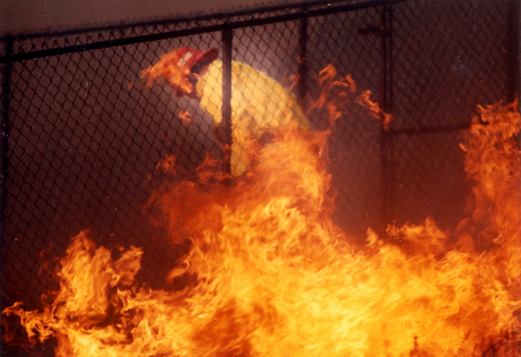. A firefighter flees through a gate to escape fast-moving flames on Blue Dane Lane in Malibu. (11/3/93)  Los Angeles Daily News file photo