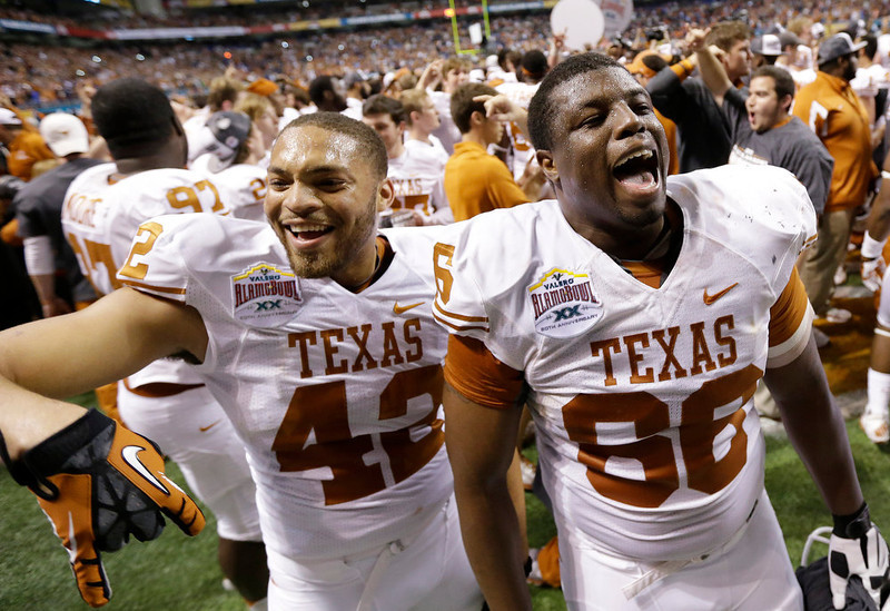 . Texas\' Caleb Bluiett (42) and Sedrick Flowers (66) celebrate following their win in the Alamo Bowl NCAA football game, Saturday, Dec. 29, 2012, in San Antonio.  Texas won 31-27. (AP Photo/Eric Gay)