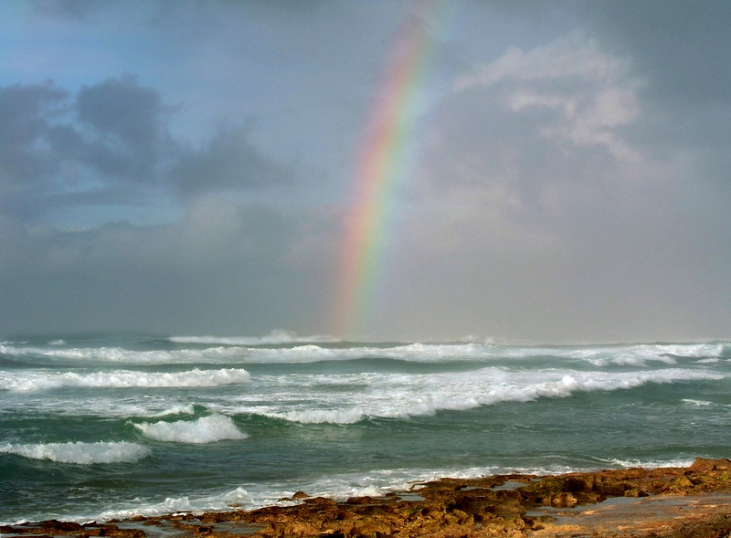 Through the dark clouds a rainbow appears  over the beautiful turquiose ocean on a stormy day  North Shore of O'ahu, Hawai'i