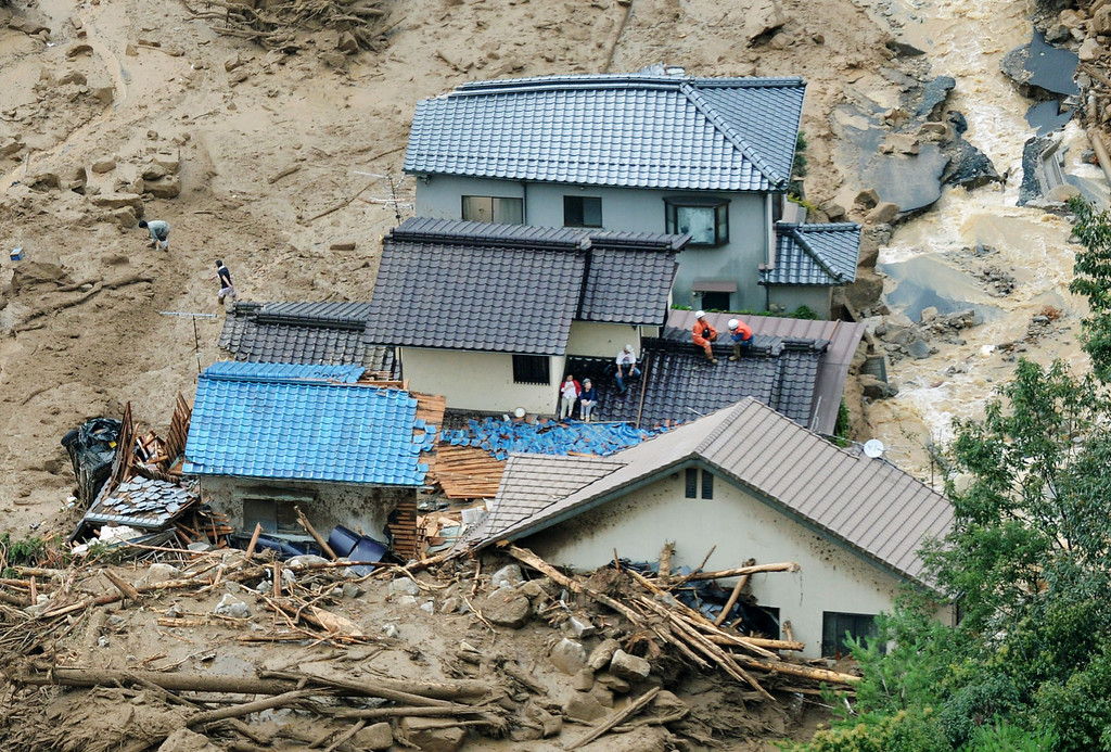 . In this aerial photo, survivors and rescue workers sit on the roof of a damaged house after a massive landslide swept through residential areas in Hiroshima, western Japan, Wednesday, Aug. 20, 2014. Rain-sodden slopes collapsed in torrents of mud, rock and debris early Wednesday in the outskirts of Hiroshima, killing at least 36 people, police said. (AP Photo/Kyodo News)