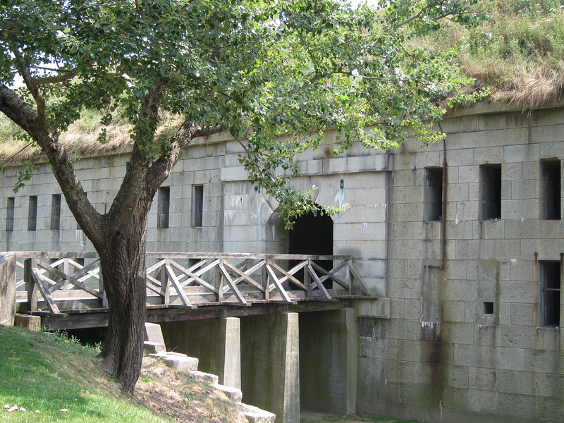 Stone block Fort Warren surrounded by trees. Take the Georges Island Ferry to visit Fort Warren.