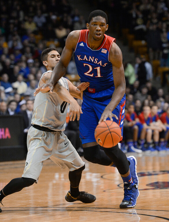 . Colorado University guard, Askia Booker, left, challenges Kansas center, Joel Embiid, for the ball in the first half of play at the Coors Events Center in Boulder Colorado Saturday afternoon, December 07, 2013. (Photo By Andy Cross/The Denver Post)