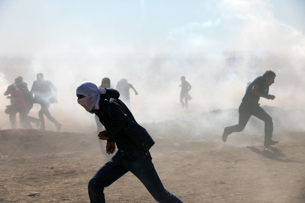 . Turkish security forces use teargas and water cannons to disperse protesting local people as several hundred Syrian refugees wait, at the border in Suruc, Turkey, Sunday, Sept. 21, 2014.  (AP Photo/Burhan Ozbilici)