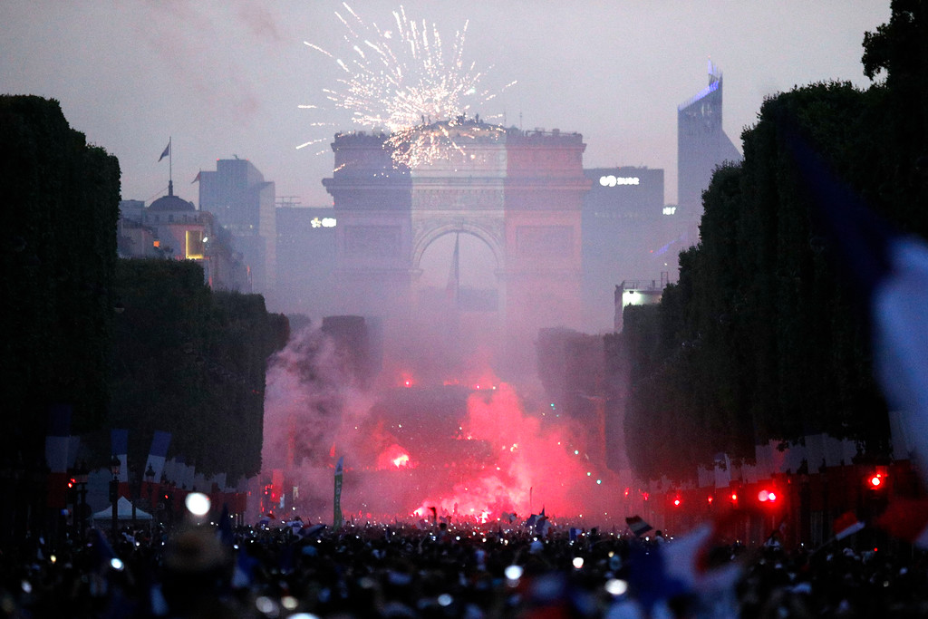 . A crowd invades the Champs Elysees avenue as the colors of France are projected onto the Arc de Triomphe in background, after France won the soccer World Cup final match between France and Croatia, Sunday, July 15, 2018 in Paris. France won its second World Cup title by beating Croatia 4-2 . (AP Photo/Francois Mori)