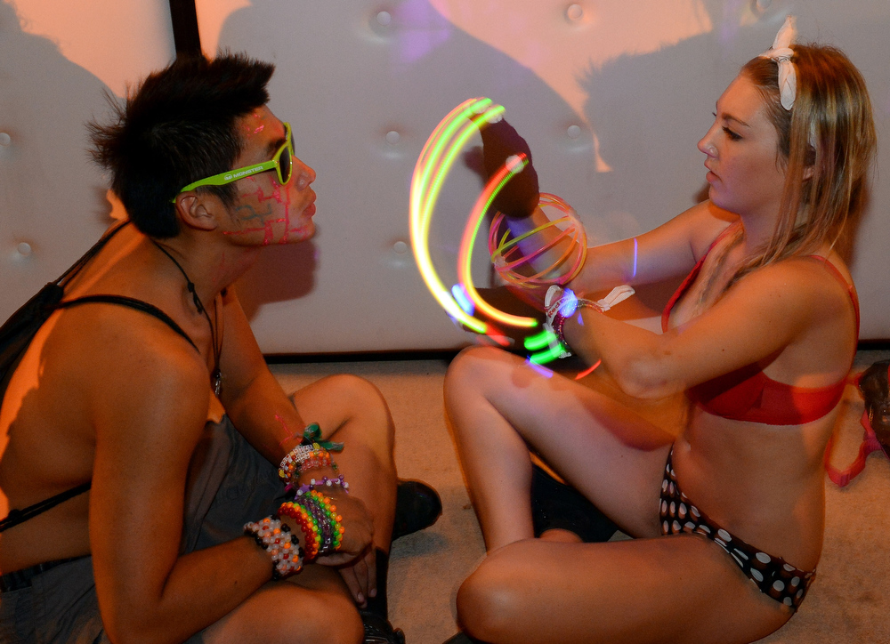 . Kingsley Chow (L) of California watches Taylor Powers of California use LED gloves at the 17th annual Electric Daisy Carnival at Las Vegas Motor Speedway on June 23, 2013 in Las Vegas, Nevada.  (Photo by Ethan Miller/Getty Images)