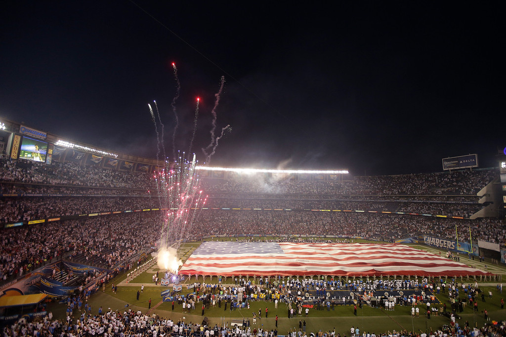 . Members of the National Guard hold up a giant American flag during the National Anthem before in an NFL football game between the San Diego Chargers and the Houston Texans Monday, Sept. 9, 2013, in San Diego. (AP Photo/Chris Carlson)
