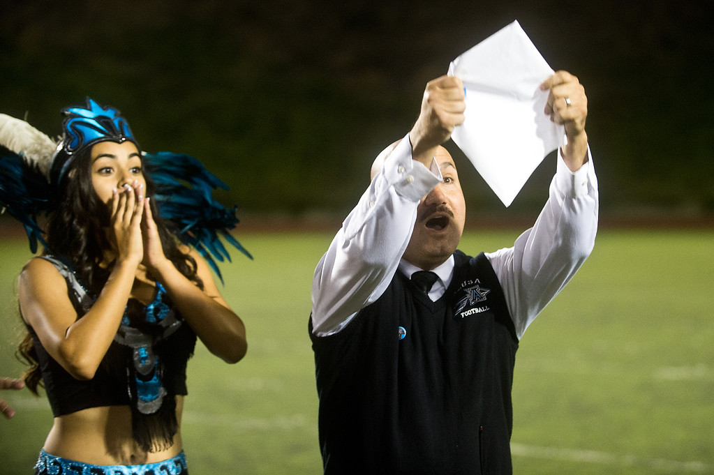 . Principal Ramiro Rubalcaba unveils the name of Azusa High 2013 Homecoming Queen during halftime of the homecoming game at Citrus College Stadium in Glendora on Friday night, Sept. 27, 2013.( Photo by Watchara Phomicinda/ San Gabriel Valley Tribune)